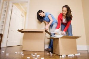Young women packing boxes, low angle view